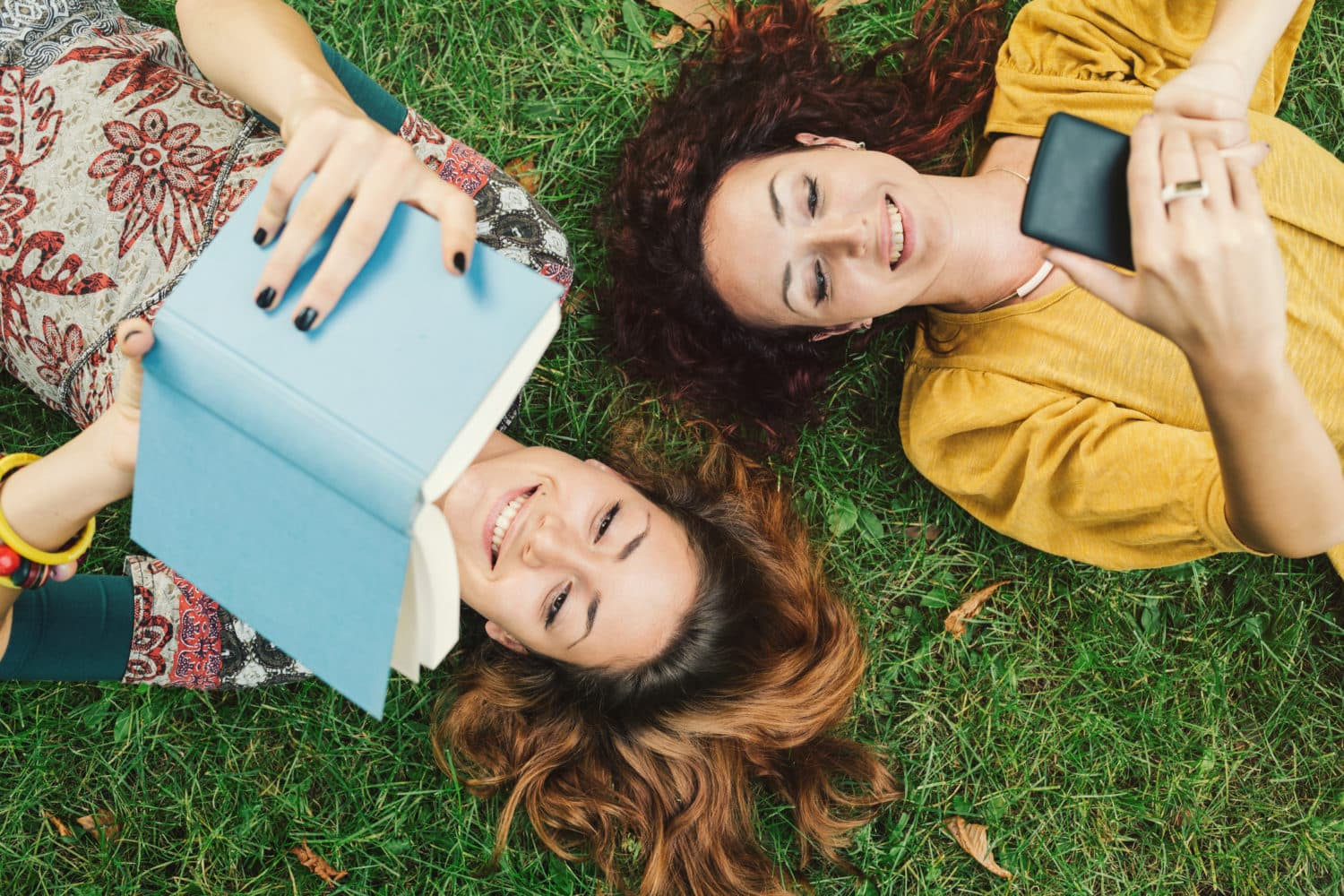 Students reading books together while laying in the grass